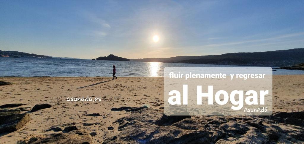 Playa con arena y rocas, mientras el sol en horas hacia su puesta se refleja en el mar. A lo lejos un caminante hacia la izquierda.  Caja de texto con: fluir plenamente y regresar al Hogar por AsunAdá y web www.asunada.es
