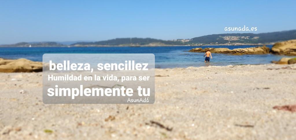 """Arena de playa hacia fondo niño metiéndose en agua y más allá, pasado el mar pueblos sobre montañas con caja de texto """"Belleza, Sencillez, Humildad en la vida para ser simplemente tú"""" por AsunAdá y web www.asunada.es"""