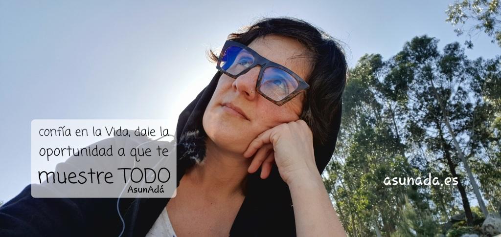 Autorretrato mirando al cielo con gafas y capucha negra, detrás unos eucaliptos altos con caja de texto: confía en la Vida, dale la oportunidad a que te muestre TODO, por AsunAdá y la web www.asunada.es