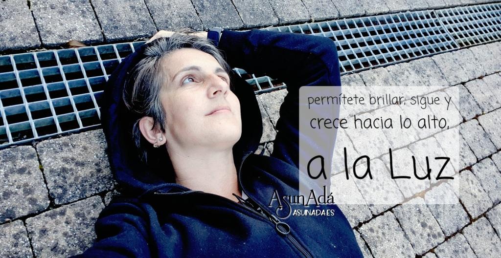 Autorretrato de medio cuerpo en el suelo tumbada con caja de texto: permítete brillar, sigue y crece a lo alto, a la Luz, por AsunAdá